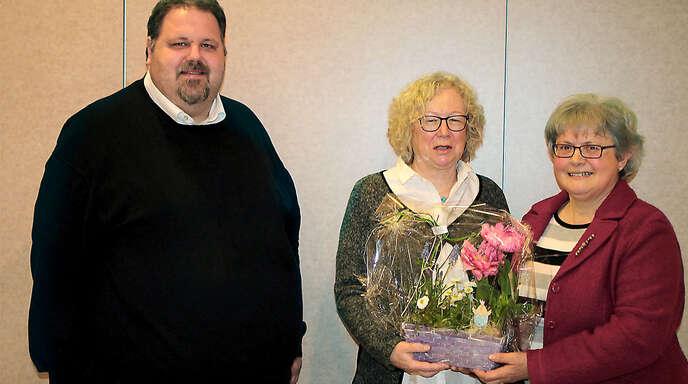 Johanna Gassmann (rechts) überreichte Dekanatsbezirksvorsitzenden Rosa-Maria Rößler (Mitte) ein Blumengebinde. Pfarrer Steffen Jelic rief zum Optimismus auf.