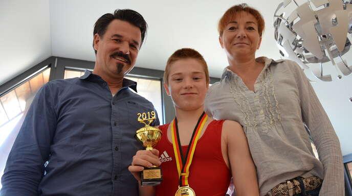 Ruben Kallfaß mit Pokal und den Eltern Ekkehard und Juliane.