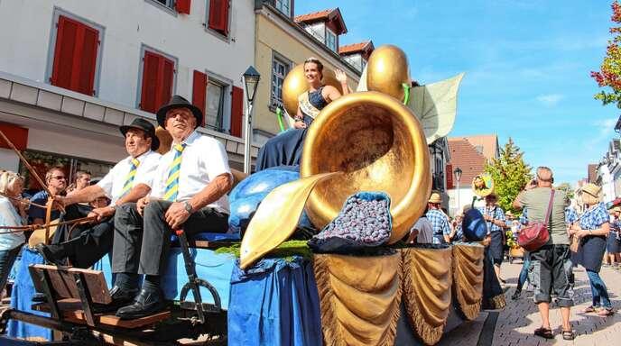 Zwetschgenkönigin Jessica winkt von ihrem prachtvollen Festwagen aus den Besuchermassen zu.