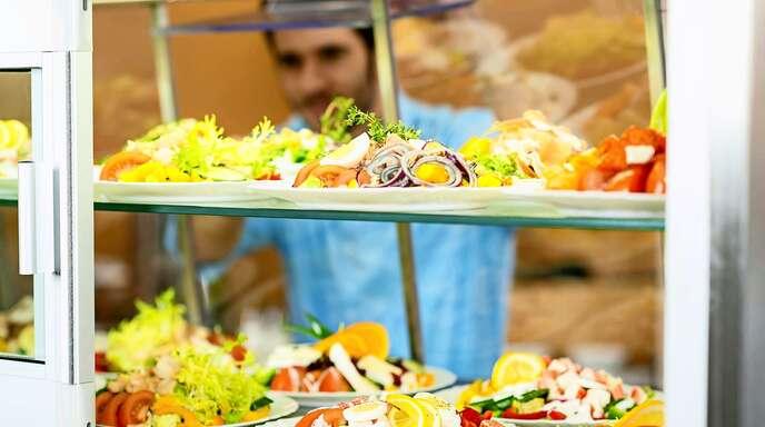 Ein Kantinenmitarbeiter schiebt zubereitete Salate in die Auslage.