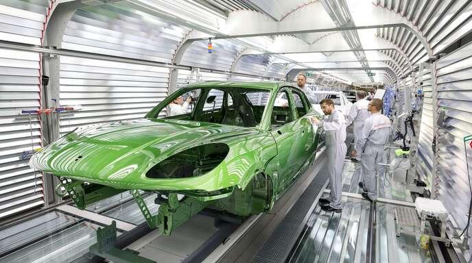Ein Mitarbeiter prüft im Werk Leipzig den Lack eines Porsche Macan.