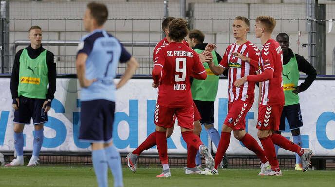 Während die Freiburger Joker Nils Petersen (2. v. r.) zu seinen Treffer mit dem ersten Ballkontakt beglückwünschen, ist Gladbachs Patrick Herrmann (vorne links) sichtlich bedient.
