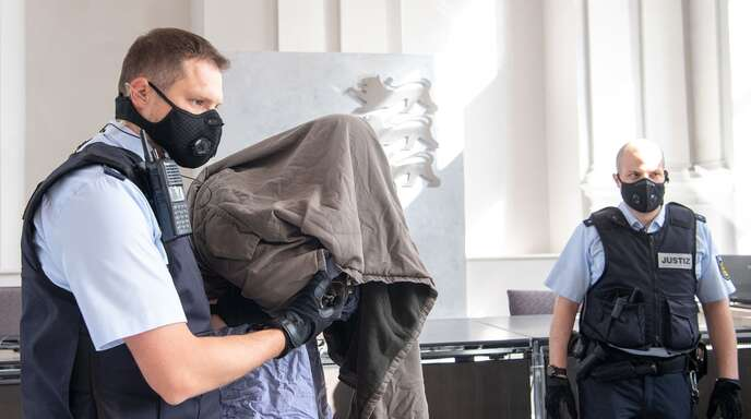 Der Angeklagte verbirgt sein Gesicht vor den Kameras.