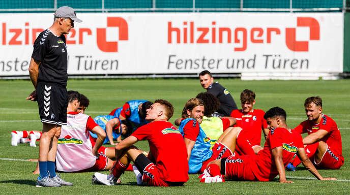 Cheftrainer Christian Streich (l., stehend) unterhält sich beim Trainingsauftakt des SC Freiburg mit dem Spieler Philipp Lienhart.