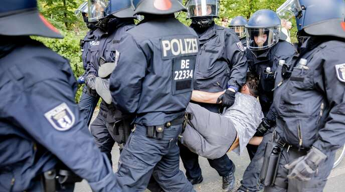 Polizisten tragen bei einer Kundgebung gegen die Corona-Beschränkungen auf der Straße des 17. Juni einen Mann.