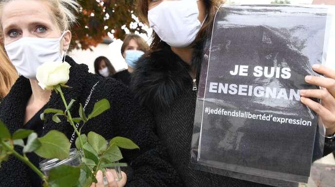 Nach dem brutalen Mord an einem Lehrer in der Nähe von Paris zeigen Franzosen ihre Solidarität. Auf dem Schild steht, dass die Meinungsfreiheit verteidigt werden muss.