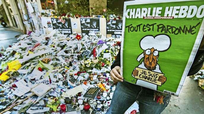 Selbst dem Propheten kamen die Tränen: eine Frau zeigt im Januar 2015 vor einer Gedenkstätte in der Nähe der Charlie-Hebdo-Redaktion in Paris das Titelbild der ersten Ausgabe nach den Anschlägen.