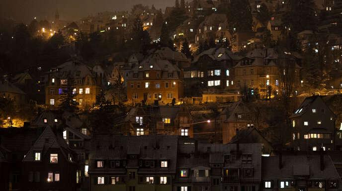 Fenster sind in Wohngebäuden in der Stuttgarter Innenstadt am Abend hell erleuchtet.