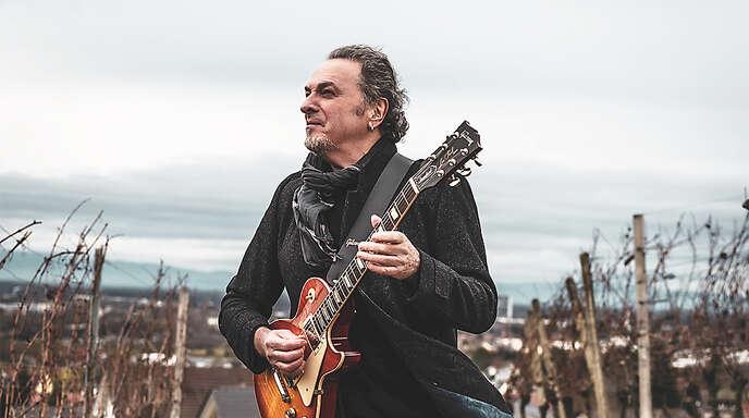 Ein Rockmusiker wirft sich in Pose: Peter Oehler mit Gitarre beim Fotoshooting in den Weinbergen bei Offenburg.