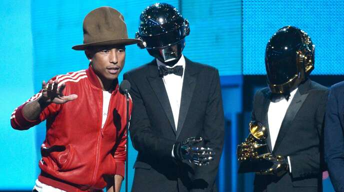 """Bei den Grammy Awards 2014 in Los Angeles bekommt Pharrell Williams (links) mit Daft Punk (Thomas Bangalter, Mitte, und Guy-Manuel de Homem-Christo) einen Preis für """"Get Lucky""""."""