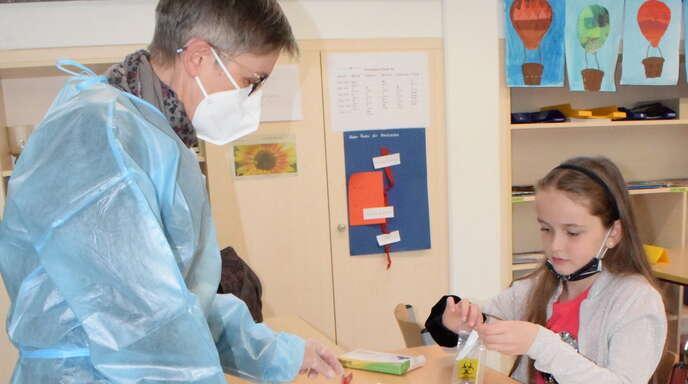 Die Handhabung von Stäbchen und Teststreifen haben diese Grundschüler in Lauf gut im Griff. Schulleiterin Manuela Seydel und Brigitte Weber (links, in Schutzkleidung) leiten sie an.