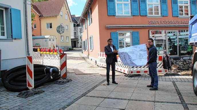 """Das Fernwärmekonzept wird komplettiert. Das Bild zeigt Bürgermeister Bernd Siefermann (links) und Projektleiter Andreas Huschle mit der Planung. Neu angeschlossen werden links das Rathaus, hinten das """"Musikerhus"""" und rechts das Simplicissimushaus."""