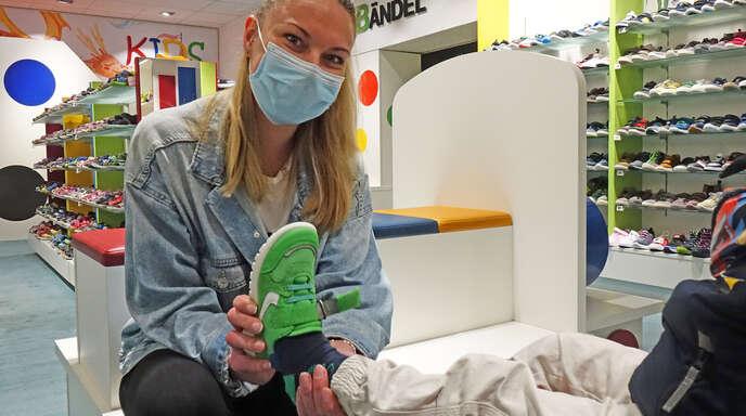Sarina Freter, Sozialpädagogin aus dem Jugendtreff Badhiesel, hilft einem Jungen im Schuhgeschäft Schubändel, in einen giftgrünen Turnschuh zu schlüpfen.