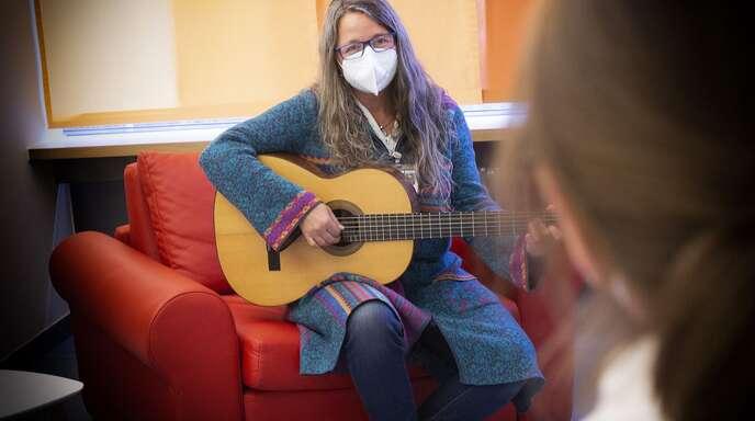 Singen ist wegen Corona nicht erlaubt, und so summt Sabine Rachl unter ihrer Maske zum Spiel der Gitarre.