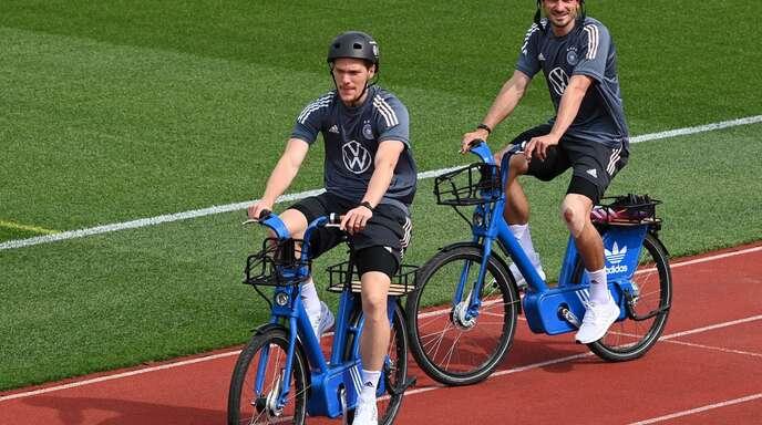 Lässig mit dem E-Bike zur ersten nationalen Trainingseinheit: Marcel Halstenberg (links) und Mats Hummels