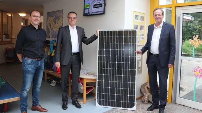 Grüner Strom für den Kindergarten Schwester Giovanna: Unser Foto zeigt Herbert Birk, Stadtwerke-Chef Erik Füssgen und Oberbürgermeister Matthias Braun mit einem PV-Modul vor dem Anzeigedisplay der Photovoltaikanlage (von links).