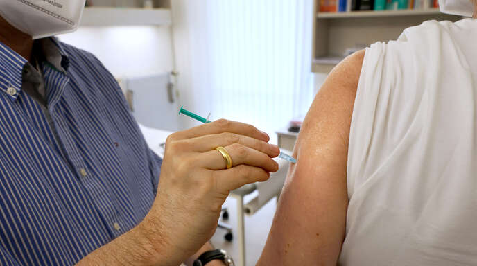 Ein Arzt impft eine Patientin gegen das Coronavirus.