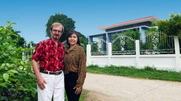 """Robert Rischmann (71) und seine Ehefrau """"Katty"""" (50) vor ihrem Wohnhaus in Thailand, das sie nach eigener Planung und Bauleitung mit viel Eigenleistung und Verwandtschaftshilfe selbst gebaut haben."""