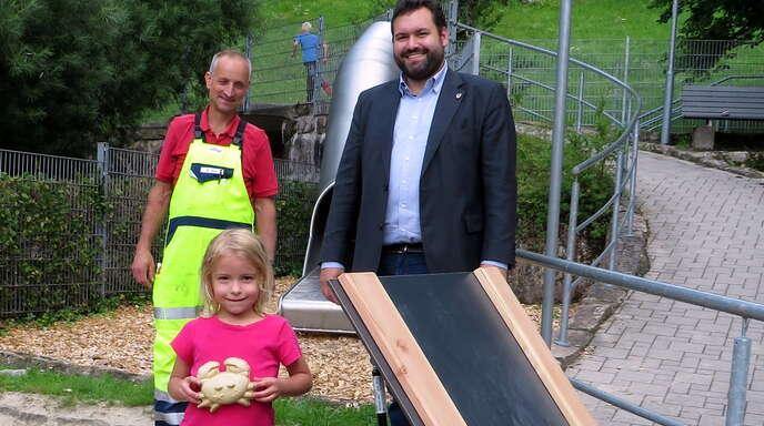 Bürgermeister Matthias Bauernfeind (rechts) und Bauhofmitarbeiter Martin Sum übergeben eine Sandelkiste auf dem Spielplatz Walke.