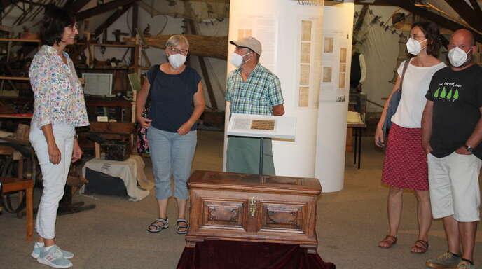 Michaela Karl, Vorsitzende des Arbeitskreises Altenheim im Historischen Verein Neuried (links), erklärt einer Besuchergruppe die Zunftlade.