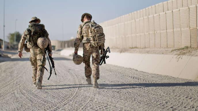 Soldaten der Bundeswehr gehen am 06.10.2013 mit ihrer Ausrüstung durchs Feldlager in Kundus in Afghanistan.