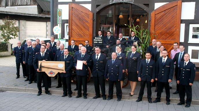 Die Kameraden der Abteilung Eckartsweier überreichten ihrem Ehren-Abteilungskommandanten Erich Nagel eine historische Feuerwehraxt, die auf einer Schautafel montiert ist.
