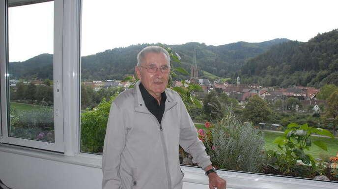 Karl Schmider, der heute seinen 80. Geburtstag feiert, auf seinem Wintergarten mit der Mauritiuskirche im Hintergrund, in der sich am Sonntag beim Mauritiuskonzert vorwiegend junge Sänger und Musiker vor ihm und seinem Werk verneigen werden.