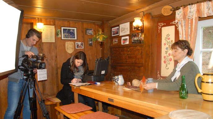Kameramann Florian Lengert und Aufnahmeleiterin Carrie Stadelmann setzen in der Stube des Naturfreundehauses »Lassgrund« die Hausacherin Billy Sum-Herrmann für das Dialekträtsel der Fernsehserie »ARD-Buffet« ins Szene.