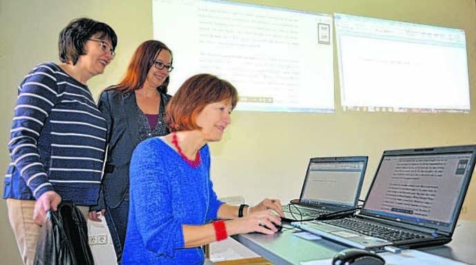 Übersetzerin Maja Überle-Pfaff lässt sich am Computer von Sibylle Reiff-Michalik (Leiterin der Stadtbibliothek Offenburg, links) und Petra Bös (Projektleiterin »Gläserne Übersetzer«) über die Schulter schauen.