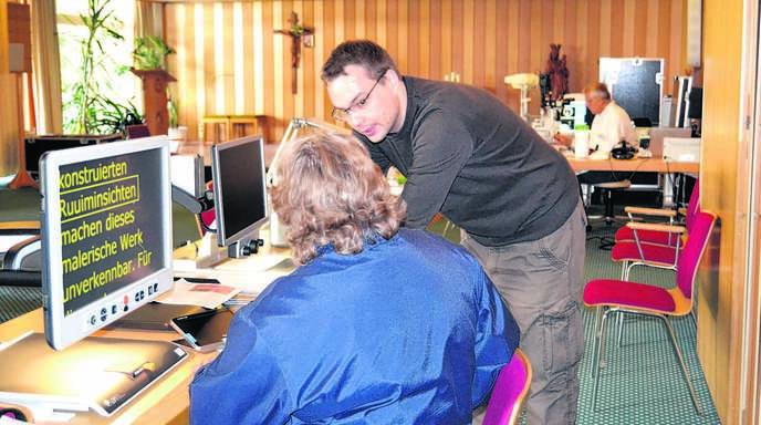Klaus-Martin Beskes erläutert die Handhabung eines Bildschirmlesegerätes, im Hintergrund arbeitet Augenarzt Rainer Dünzen.