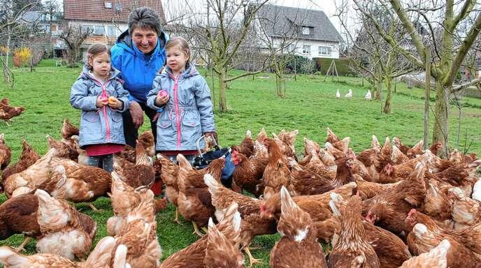 Eierkauf direkt bei den Hühnern: Die dreijährige Amelie (links) und ihre Schwester Marlene haben von Wilma Hildenbrand noch ein paar Ostereier dazu bekommen.