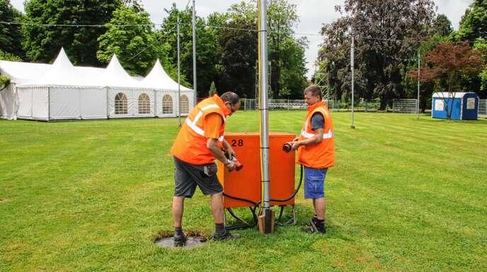 »Badens schönste Arena« im Stadtgarten wird für Fußballfans vorbereitet: Die Bauhofmitarbeiter Joachim Litsch (links) und Ralf Kraus installieren die Elektrik.
