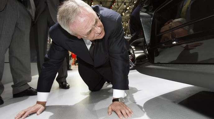 Martin Winterkorn schaut bei einer Messe unter einen Porsche GT2.