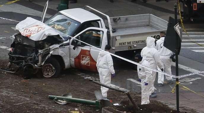 Polizisten untersuchen den stark beschädigten Pick-up-Truck, mit dem ein Mann im Südwesten Manhattans auf einen Fußgänger- und Fahrradweg gefahren ist und mehrere Menschen getötet und verletzt hat.
