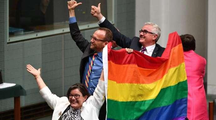 Die Parlamentsmitglieder Cathy McGowan, Adam Brandt und Andrew Wilkie präsentieren in Canberra eine Regenbogenfahne.