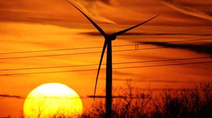 Die Silhouetten eines Windrades und einer Hochspannungsleitung zeichnen sich vor einem farbenprächtigen Himmel ab.