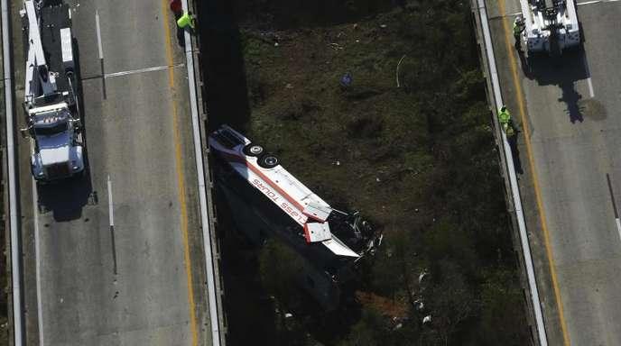 Rettungskräfte schauen auf einen verunglückten Bus hinab. Der Bus hatte eine Schüler aus Texas auf dem Rückweg aus Disney World an Bord.