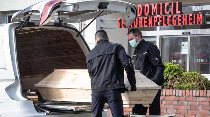 Mitarbeiter eines Bestattungsinstituts heben den Sarg des Todesopfers in ihr Fahrzeug.