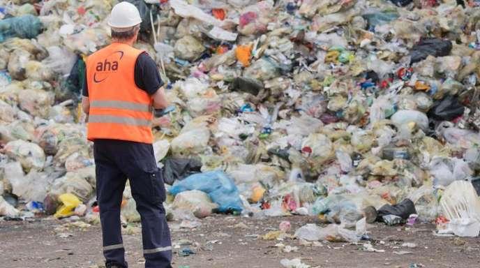 Ein Mitarbeiter einer Deponie vor einem Müllberg: In der Gelben Tonne landet oft Müll, der dort gar nicht hingehört.