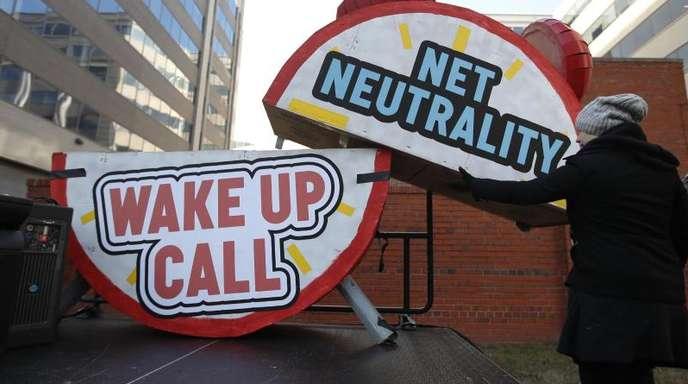 """Ein Mann baut bei einer Protestaktion vor dem Gebäude der Telekommunikationsaufsicht FCC in Washington einen riesigen Wecker ab, auf dem """"Netzneutralität"""" und """"Weckruf"""" geschrieben steht."""