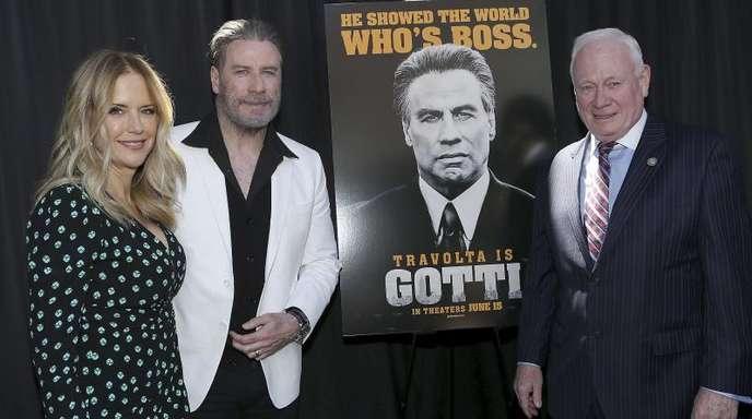 John Travolta, seine Frau Kelly Preston (l) und Marty Golden (r), Mitglied des Senats des Bundesstaats New York, neben einem Poster zu Travoltas neuem Film «Gotti» in Brooklyn.