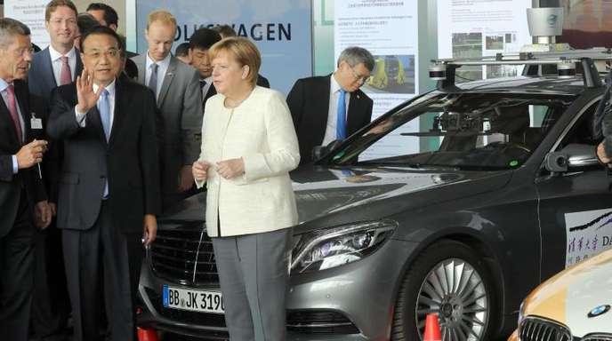 Li Keqiang, Ministerpräsident von China, und Bundeskanzlerin Angela Merkel informieren sich auf dem ehemaligen Flughafen Tempelhof bei einer Präsentation über das autonome Fahren.