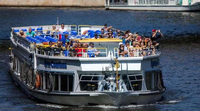 Touristen sind mit einem Ausflugsgsschiff auf der Spree in Berlin unterwegs.