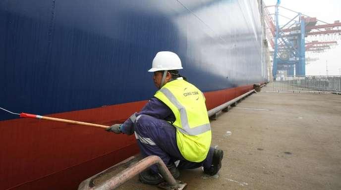 Schönheitsarbeiten am Rumpf eines Containerschiffs in Hamburg. Auf die Schifffahrt kommen Umstellungen zu.