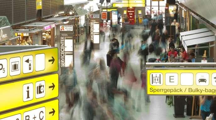 Passagiere laufen mit ihrem Gepäck durch einen Flughafen.