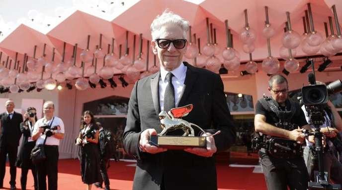 David Cronenberg mit dem Ehrenlöwen vor dem Festivalgebäude auf dem Lido.