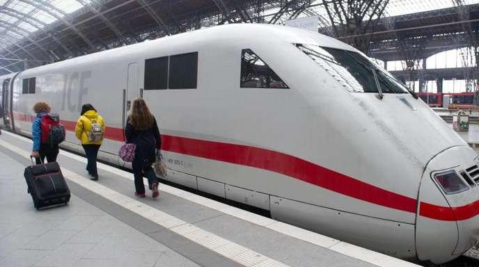 Reisende gehen im Hauptbahnhof in Leipzig an einen ICE vorbei.