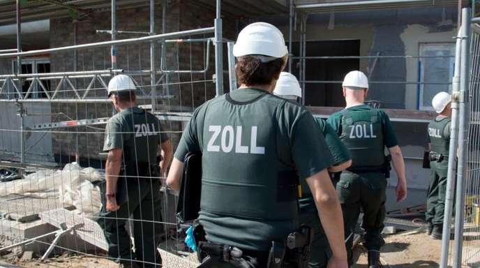 Zollbeamte betreten bei einer Razzia gegen Schwarzarbeit eine Baustelle.