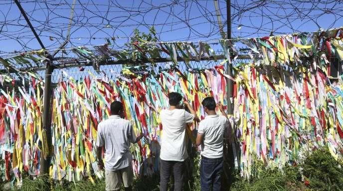 Menschen hängen Spruchbänder mit dem Wunsch zur Wiedervereinigung zwischen Nord- und Südkorea nahe der Grenze zu Nordkorea auf.