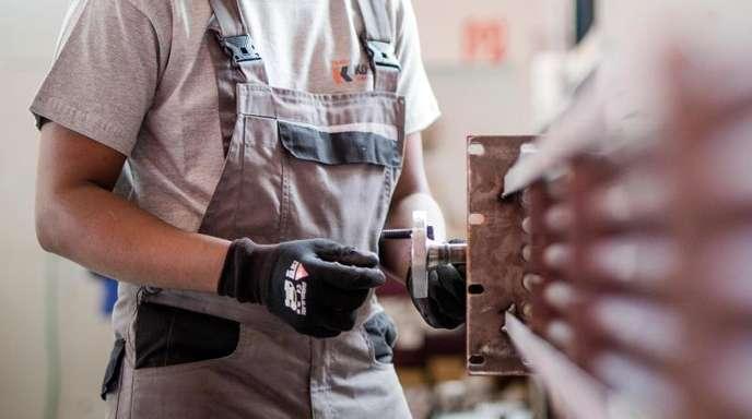Ein Flüchtling arbeitet während eines Praktikums bei einem Industrieunternehmen in der Produktion.